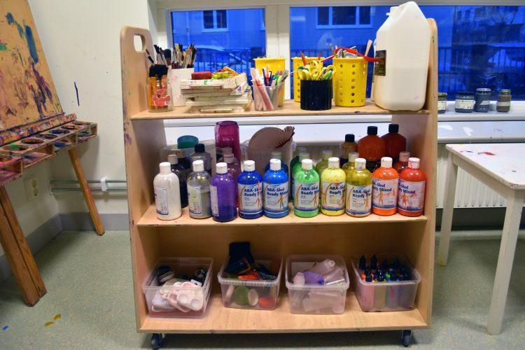 Målarburkar, pennor, saxar och andra verktyg står på en vagn i ateljén på Ribersborgs förskola.
