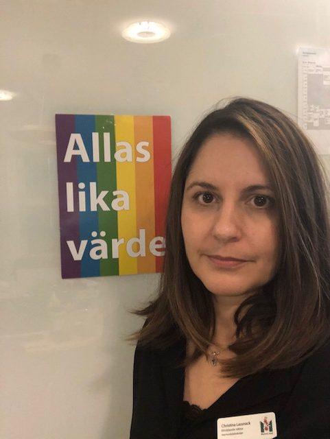 Kvinna står framför ett papper på väggen där det står: Allas lika värde.