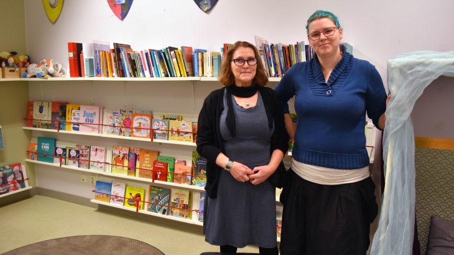 Barnskötare Agneta Zeberg och förskollärare Stephanie Persson på Ribersborgs förskola står framför en bokhylla i förskolans bibliotek.
