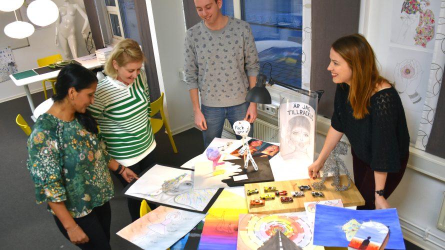 """Sara Olausson, hemkunskapslärare, Kristina Åkesson, bildlärare, Erik Stenlund, musiklärare och Jenny Andersen, slöjdlärare, står framför några av elevernas verk på temat """"Gränsland""""."""