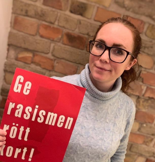 Caroline Sjölin, rektor på Apelgårdsskolan, håller i ett A4 papper där det står Ge rasismen rött kort!
