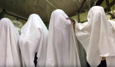 Fyra barn utklädda till spöken i vita lakan, framför en bakgrund på ett grönaktigt förfallet rum med spindelväv i taket.
