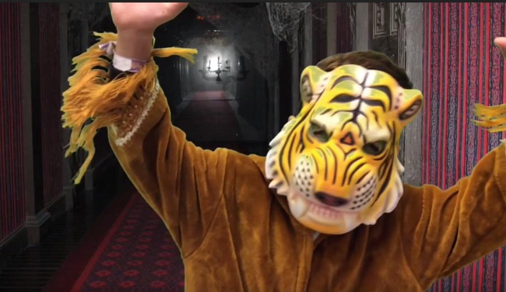 Ett barn utklädd till tiger, framför en bakgrund på en röd, spökaktig korridor.