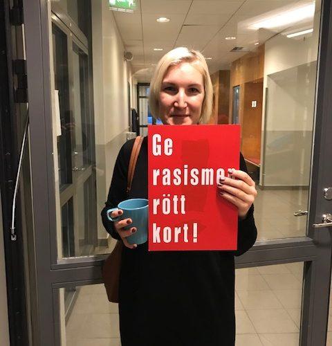 """Kvinna håller upp rött kort där det står """"ge rasismen rött kort""""."""