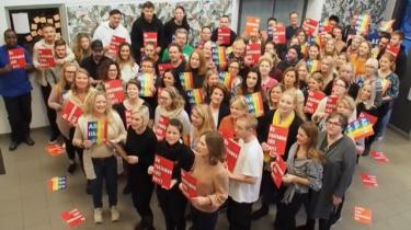 """Personal på Strandskolan håller upp rött kort där det står """"ge rasismen rött kort""""."""