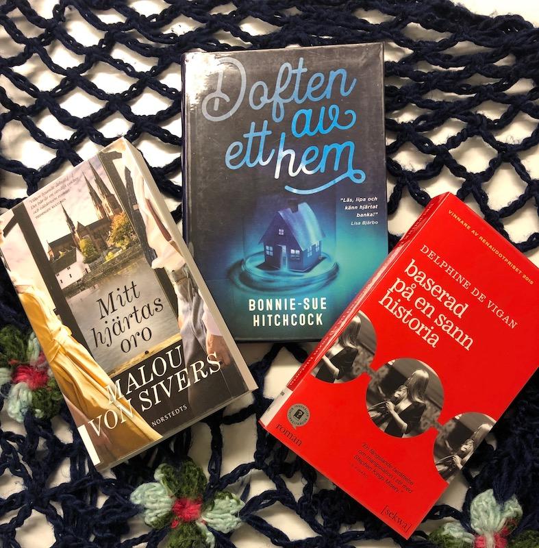 Tre böcker ligger på skrivbord.