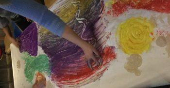 Fingrar målar med fingerfärg på stort papper.