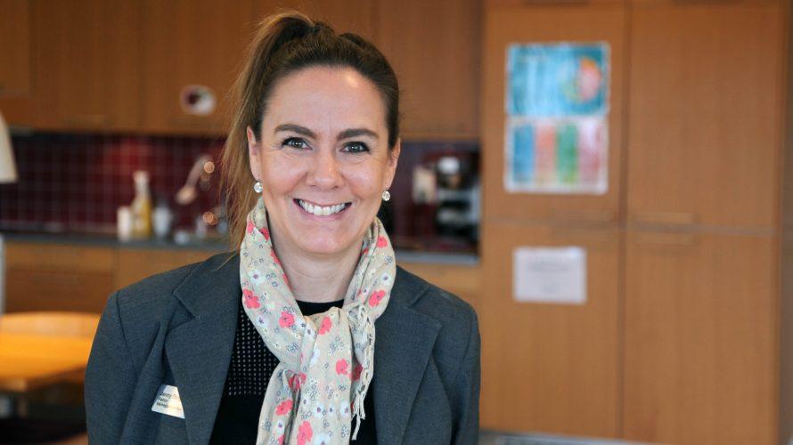 """Jenny Bergwall rektor på Bäckagårdsskolan står framför en affisch med det strategiska ramverket """"varje elevs bästa skola"""""""
