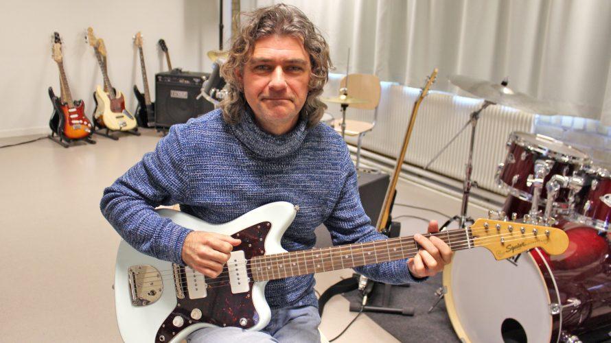Paulo De Oliveira, musiklärare på Bergaskolan, sitter på en stol och spelar på en elgitarr.