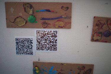 På en vägg är kartongbitar uppsatta med färgklickar och löv på. Bredvid syns QR-koder.