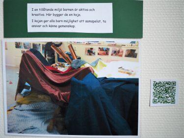 På en vägg är en bild på en koja uppsatt och en text som förklarar bilden. Bredvid bilden sitter en QR-kod.