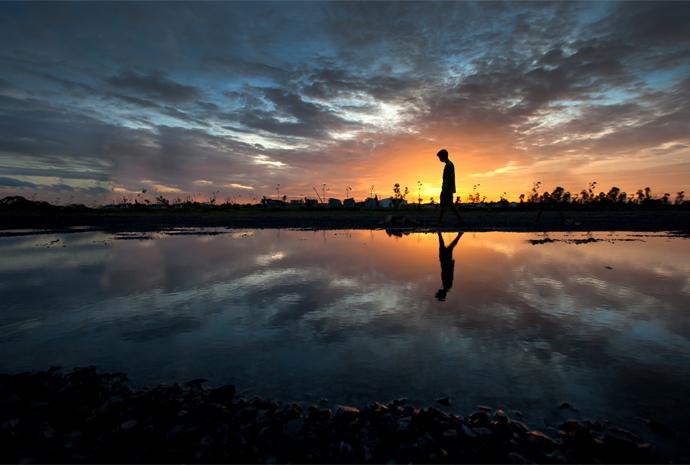 Pojke står i solnedgång vid tjärn.