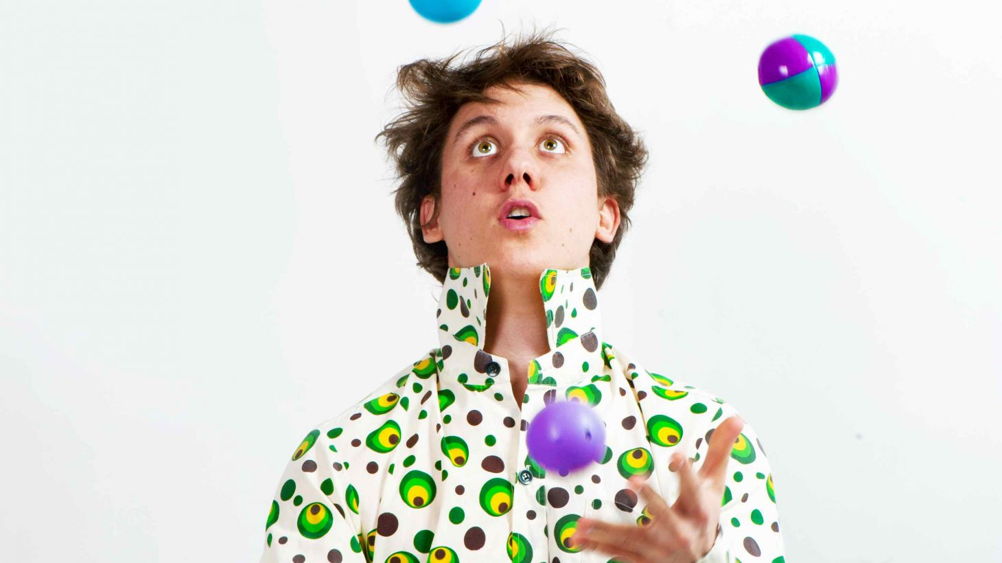 Man jonglerar med färgglada bollar.