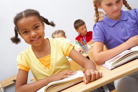 Elever sitter i skolbänkar med uppslagna böcker framför sig.