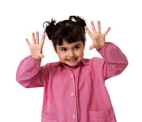 Flicka håller upp händerna framför sig.