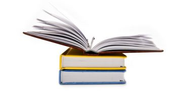 Tre böcker ligger på hög och den översta är uppslagen.