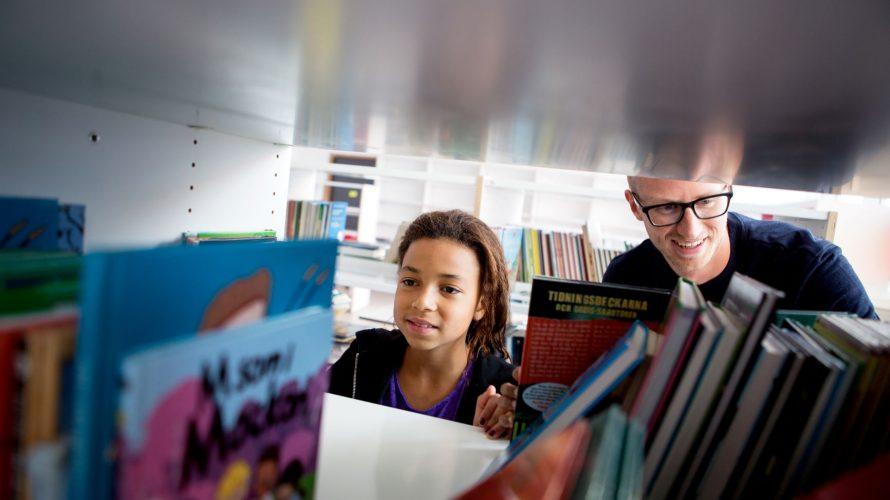 Man och elev tittar på böcker i bokhylla.