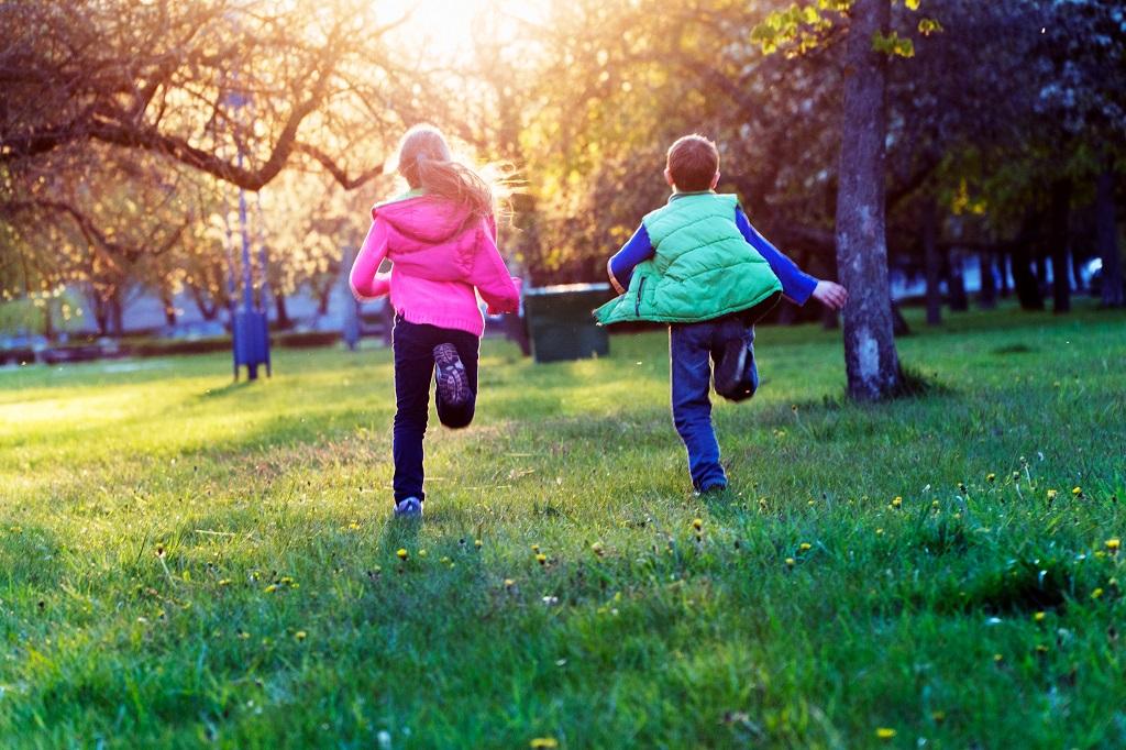Två barn springer i solnedgång på en grön gräsmatta