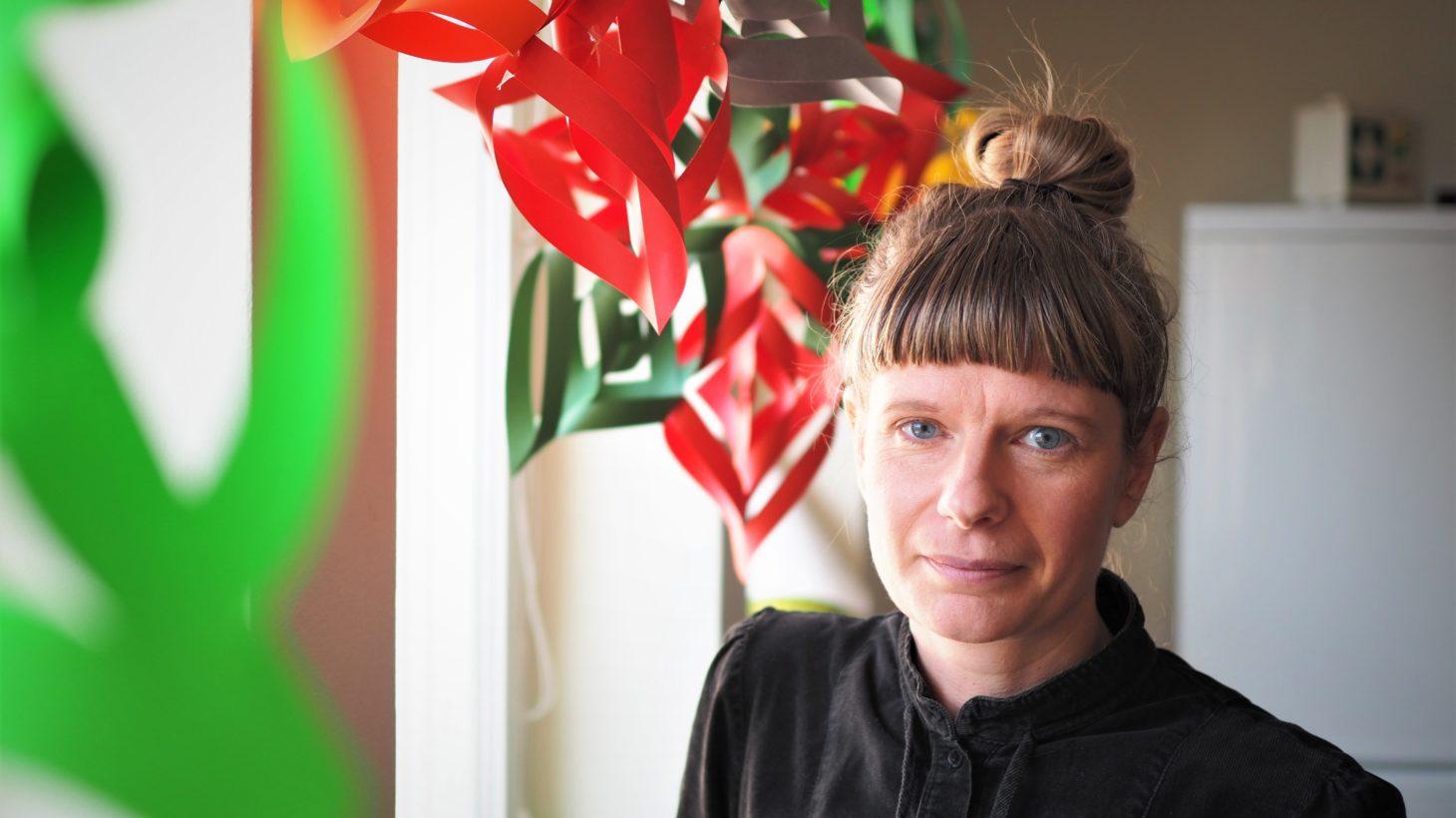 Camilla Adolfsson, lärare på Valdemarsro gymnasium. står vid ett fönster och tittar mot kameran.