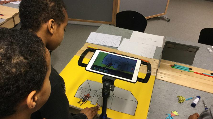 Två barn använder ipad för att animera.