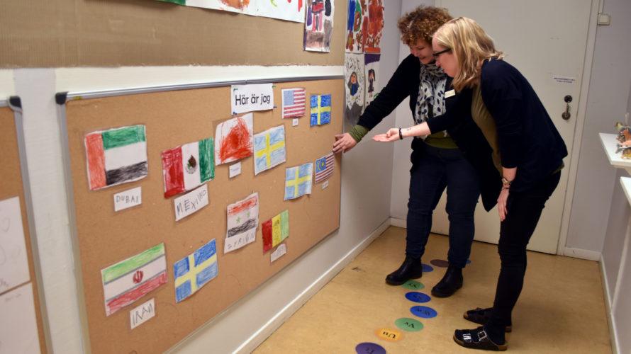 Pedagoger sätter upp flaggor på en anslagstavla.