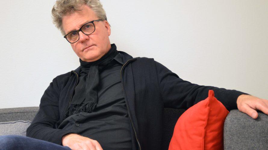 Håkan Wegestål sitter i en grå soffa lutad mot en röd kudde.