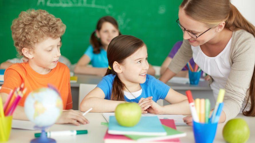 En lärare hjälper två elever vid skrivbord