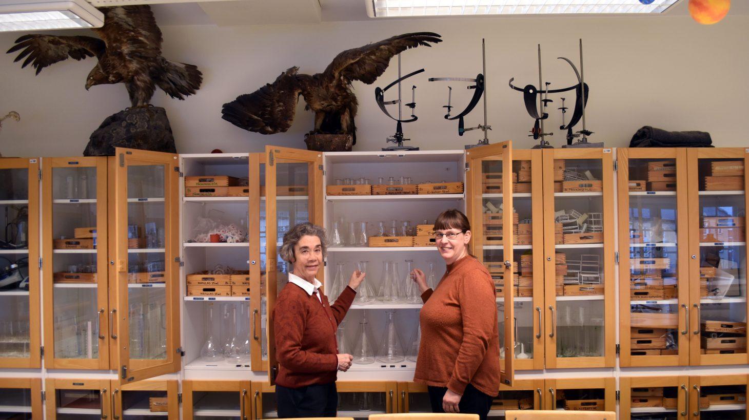 Eva Cederberg och Eva Månsby, NO-lärare på S:t Petri skola, står framför ett träskåp fyllt av mätglas i en laborationssal.