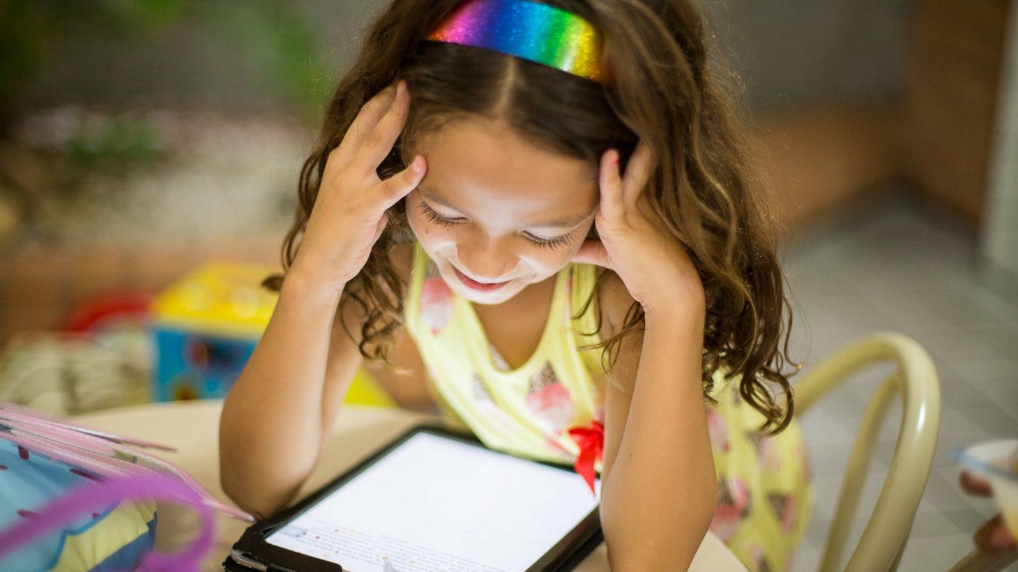 Barn läser bok på läsplatta