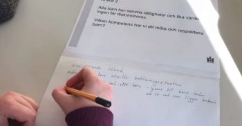 En hand skriver på ett papper om barnkonventionen