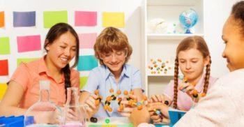 Två elever och två lärare funderar över molekylmodelll.