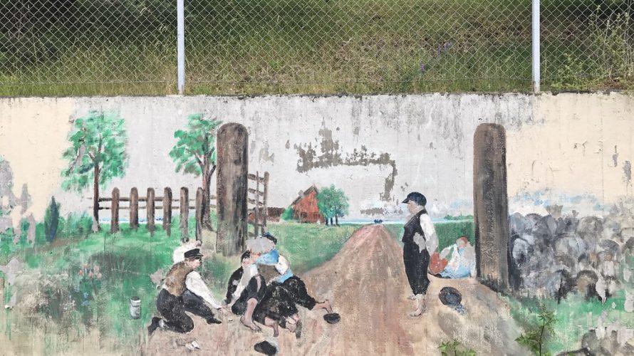 En muralmålning föreställande tavlan Grindslanten där barn slåss om en peng vid en grind.