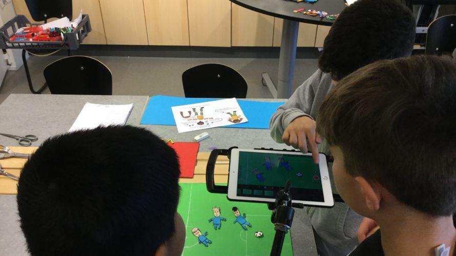 Barn tittar på läsplatta och pekar.
