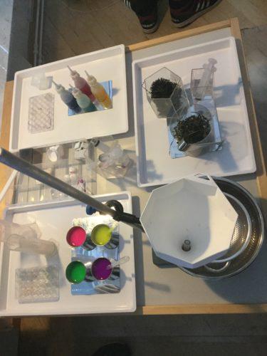 Färger och verktyg ligget på ett bord.