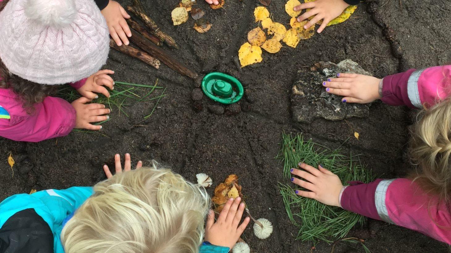 Barn håller sina händer i en cirkel där olika material finns.