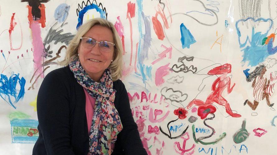 Lena Klapp sitter framför färgglada figurer som barnen har målat