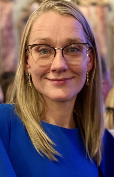 Blond kvinna med glasögon och kornblå tröja.