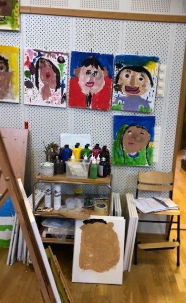 En målaratelje där det sitter tecknade porträtt på väggen.