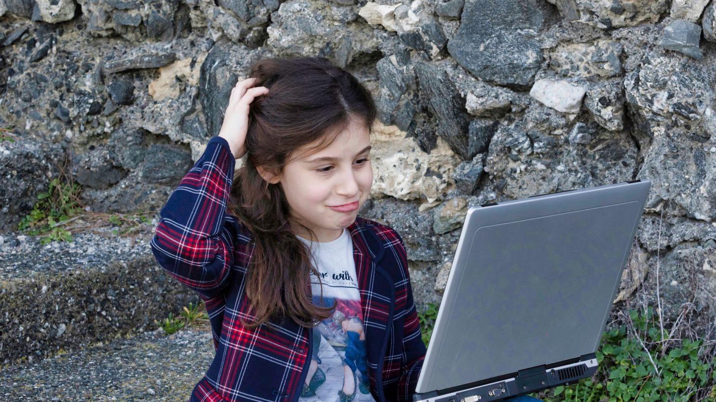 Flicka kliar sig i huvudet samtidigt som hon tittar in i en dators skärm.