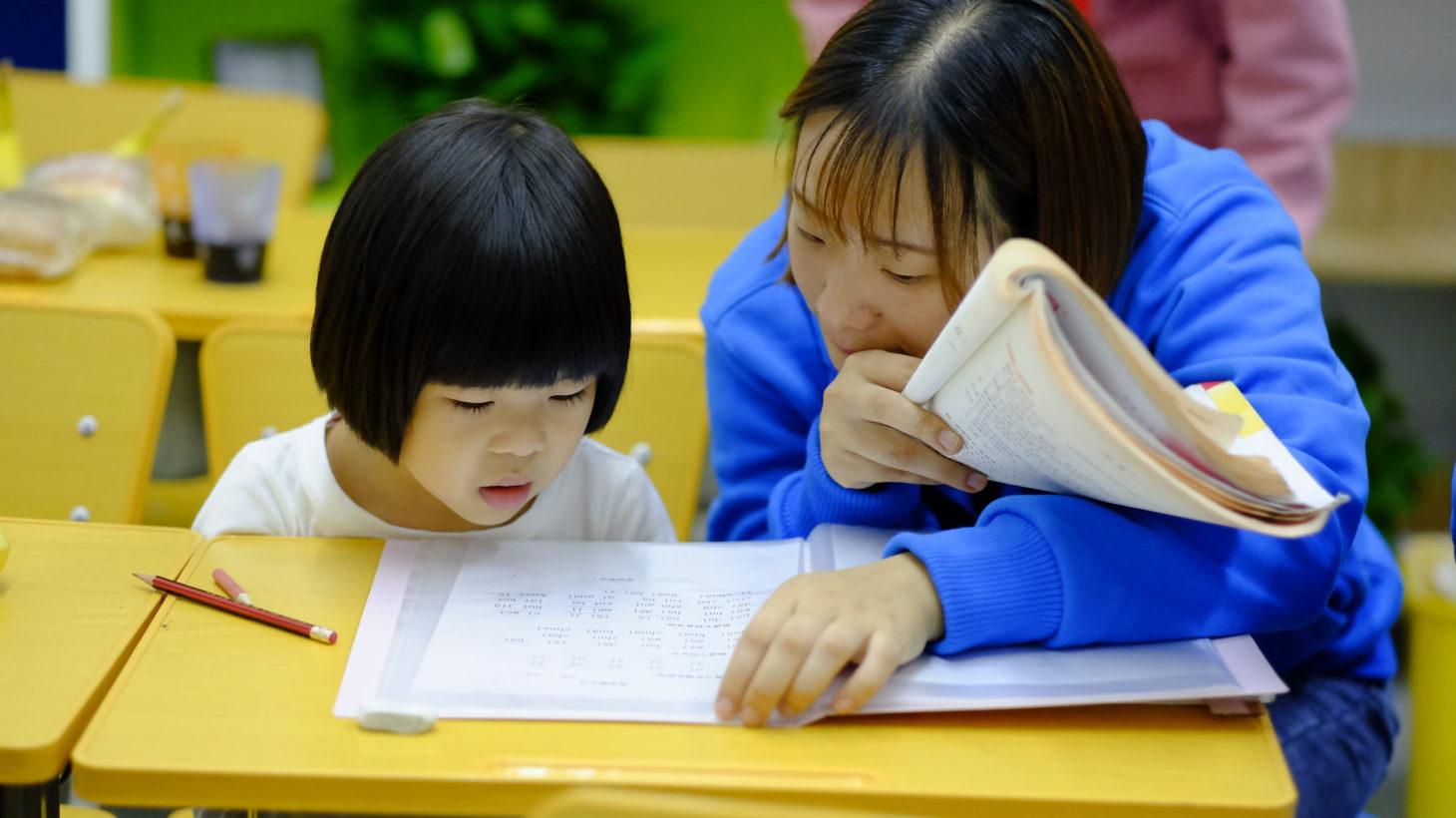 Vuxen och barn läser tillsammans.