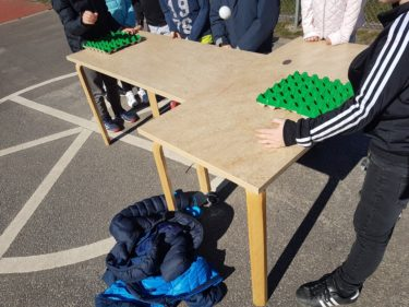 Barn studsar med en pingisboll och ska träffa en äggkartong.