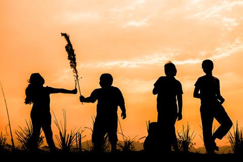 Fyra barns siluetter står i en brinnande solnedgång.