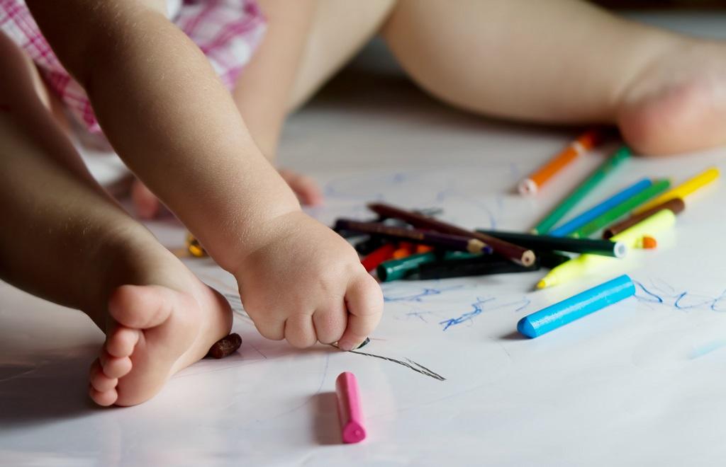 Barns händer håller i kritor och ritar på ett papper på golvet