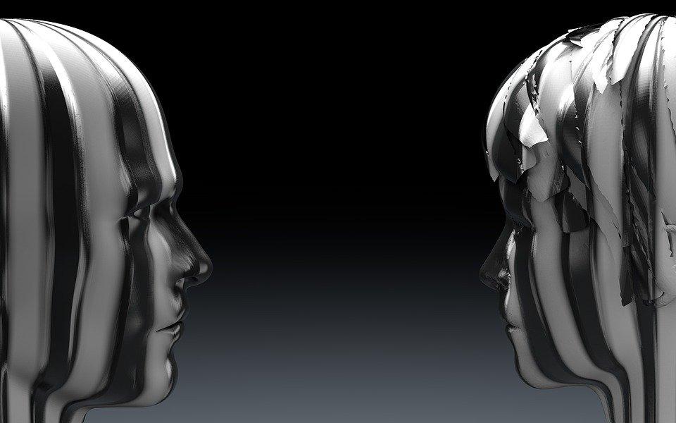 Två stiliserade barnhuvuden som står mot varandra vända i profil