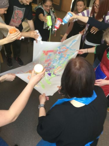 Pedagoger håller upp stort vitt papper och några av dem häller färg över pappret.