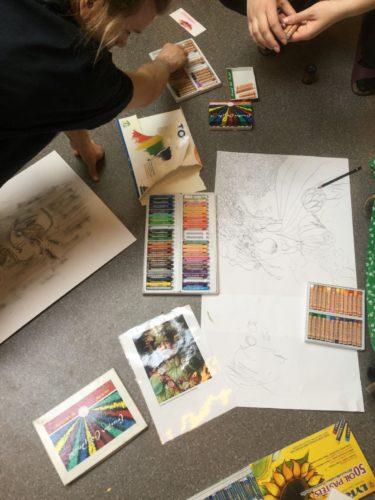 Teckningar och kritor ligger framme på golvet så att de vuxna kan måla.