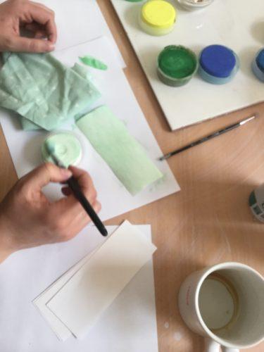 Händer målar med vattenfärger.