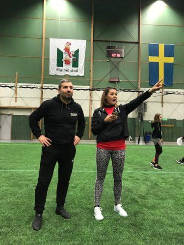 Två läare står och instruerar på en grön fotbollsplan.