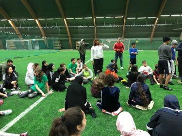 Elever sitter på en grön fotbollsplan och en lärare i mitten instruerar.