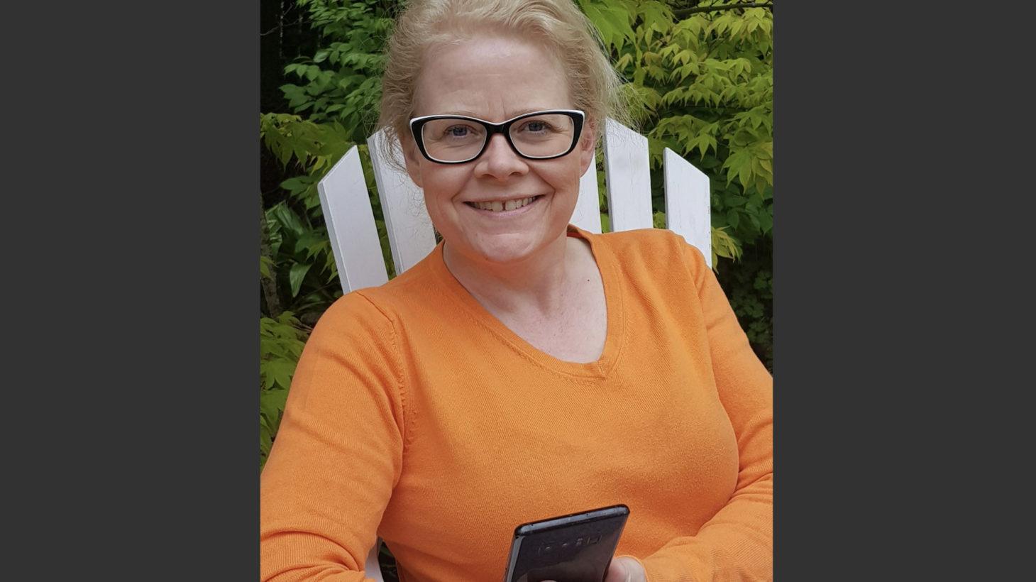 Johanna Rexgård, specialpedagog på Sjukhusskolan, håller i en mobiltelefon och tittar in i kameran.